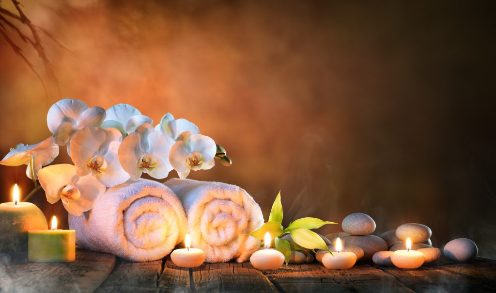 towels, pebble stones, candles, and flowers at a spa