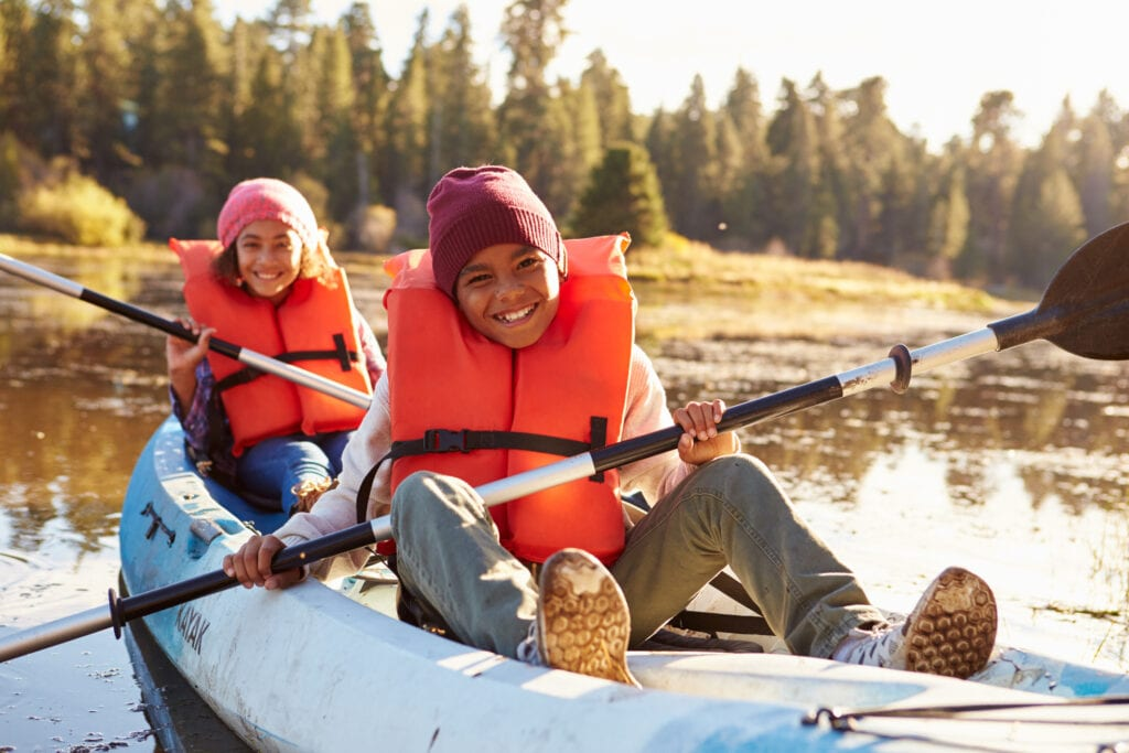 kids kayaking on a lake